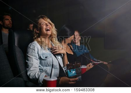 Group of friends sitting in multiplex movie theater and watching comedy movie. Young people watching movie in cinema and laughing.