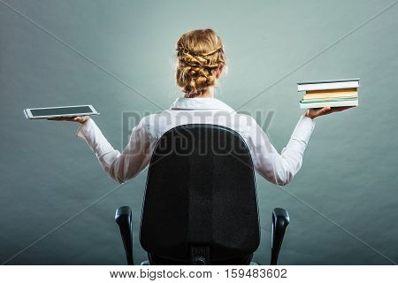 Ebook vs book. Woman sitting on chair holding traditional book and e-book reader tablet touchpad pc back view grunge background.