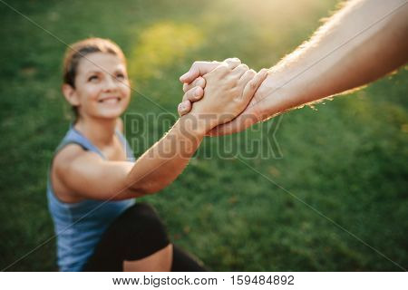 Close up shot of man helping woman to stand up. Focus on hands of couple exercising at park.