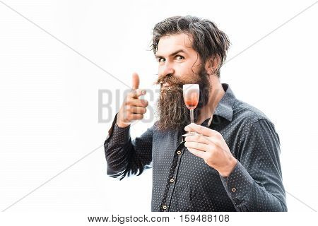 handsome bearded man with wet ruffled hair mustache and long soiled beard of liquor on funny face holding glass of red alcoholic shot and shows on it isolated on white