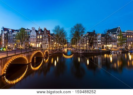 Night city view in Amsterdam Netherlands. Canal and typical dutch houses at night in Amsterdam Netherlands