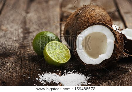 Close-up of split coconut and fresh lime on wooden background. Concept of organic nutrition and dieting.