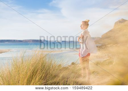 Woman, arms crossed, feeling chilled, enjoying last autumn sun, an beautiful Balos beach. Concept of vacations, freedom, happiness, enjoyment and well being.