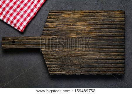 Wooden cutting board and classic red checkered textile on dark background. Top view, copy space for text