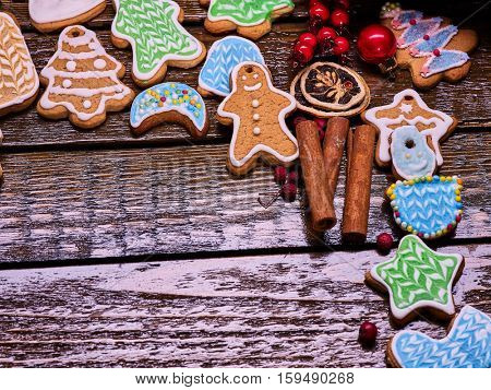 Right-hand angle of Christmas gingerbread cookies and cinnamon sticks on woden table . Background with copy spice.