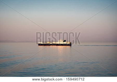 Container bulk carrier ship in a clam sea at dawn