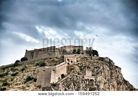 Palamidi fortress on the hillunder a cloudscape and a seagull flying above it. Nafplion - Greece