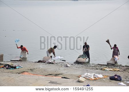 VARANASI, UTTAR PRADESH, INDIA - FEBRUARY 17, 2016 - Indian people washing their clothes in the waters of river Ganga
