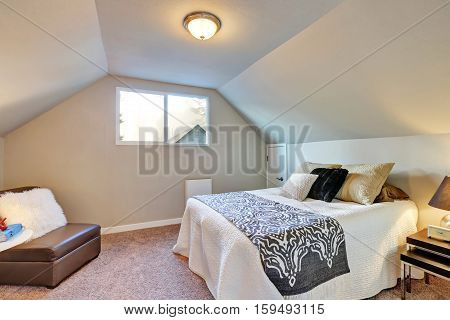 Attic Bedroom With Large Bed And Carpet Floor.