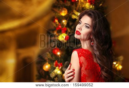 Christmas. Beautiful Smiling Woman. Elegant Sexy Lady In Red Dress Over Xmas Tree Gifts Background.