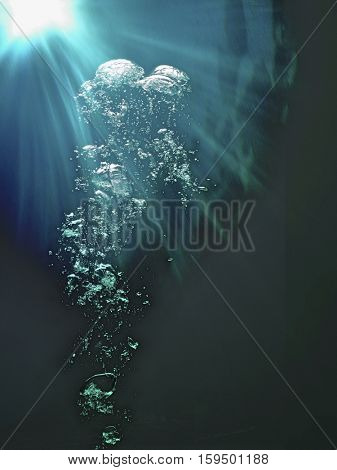 Underwater bubbles and sunlight breaking through