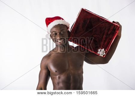 Muscular black shirtless young man in Santa Claus hat standing holding two colorful festive Christmas gifts to celebrate the season, on white