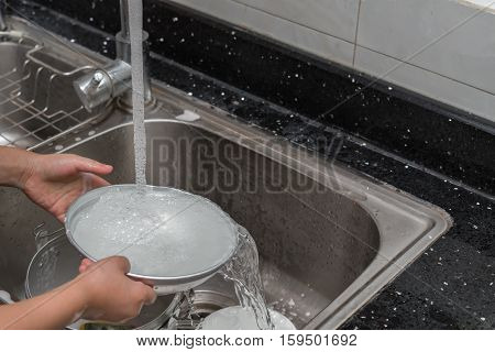 kid washing dishware in the kitchen sink with soapy sponge