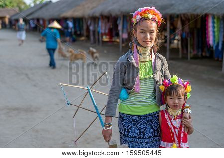 CHIANG RAI, THAILAND - FEBRUARY 4, 2016:  Karen long neck mother with kid in a village between Chiang Rai and Chiang Mai. Karen is one of several ethnic hill tribes in northern Thailand