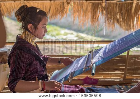 CHIANG RAI, THAILAND - FEBRUARY 4, 2016:  Karen long neck woman weaving in a village between Chiang Rai and Chiang Mai. Karen is one of several ethnic hill tribes in northern Thailand