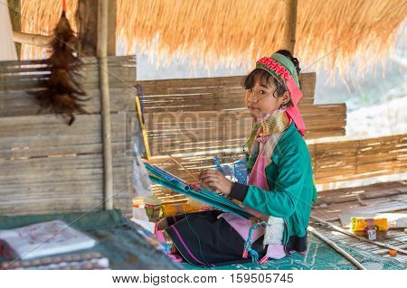 CHIANG RAI, THAILAND - FEBRUARY 4, 2016:  Karen long neck girl weaving in in a village between Chiang Rai and Chiang Mai. Karen is one of several ethnic hill tribes in northern Thailand
