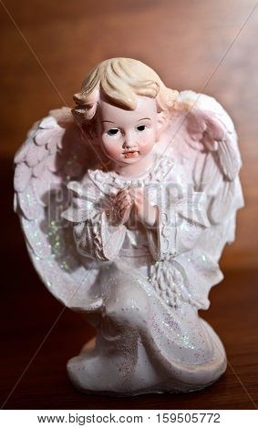 one little white guardian angel in snow on wooden background. vintage style christmas decoration
