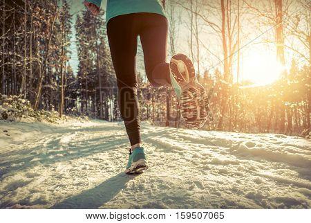Woman Running at snowly winter under sunlight.