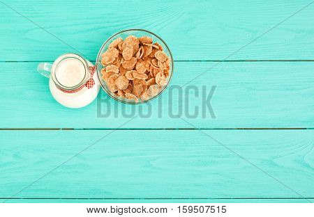 Oat flakes and jug of milk on blue wooden background. Top view