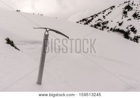Ice axe on background of snow. Tatry
