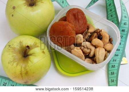 Useful food, healthy snack, lets lose weight, different nuts (cashews, walnuts) and dried apricots in a beautiful light green lunchbox to cover garden and apple on a white surface, centimeter