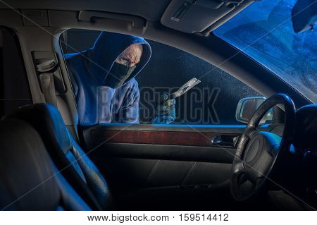Hooded thief looking to break into a car