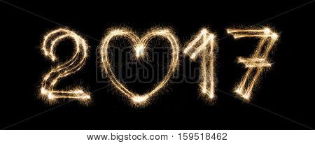 2017 New year text from sparkler firework on black background with heart shape, love symbol and greeting. Two thousand seventeen numbers. Illuminated date figures for calendar
