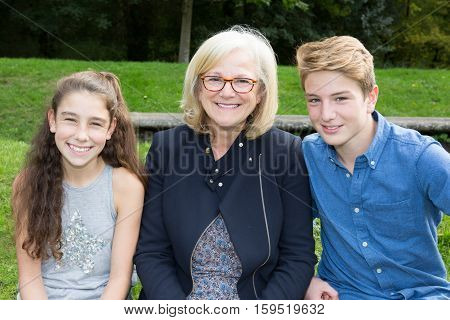 two teens with grand mother in park