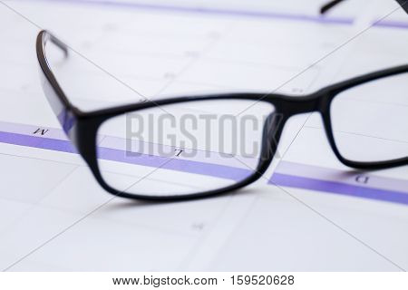 Black male business glasses in office on the desk with calendar as concept of organization and planning. Closeup.