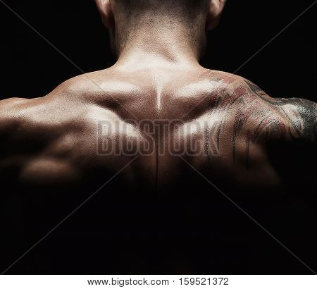 Unrecognizable man shows strong neck muscles closeup, athletic trapezius crop. Low key, studio shot on black background.