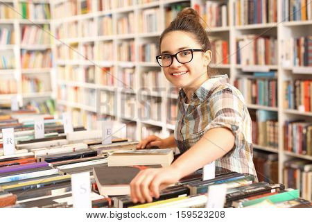The girl in the bookstore chooses the book. Schoolgirl in the library. Library, teenager  chooses a book. Student in the school library.