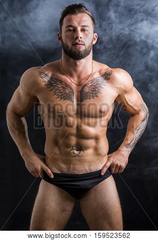 Handsome shirtless muscular man in briefs, standing, on dark smoky background