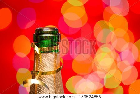Champagne bottleneck with blurred lights in background New Year celebration