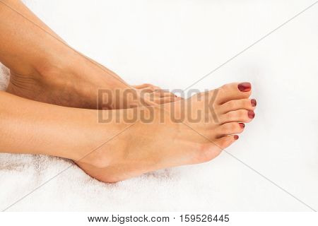 Beautiful legs of young woman with pedicure on white towel