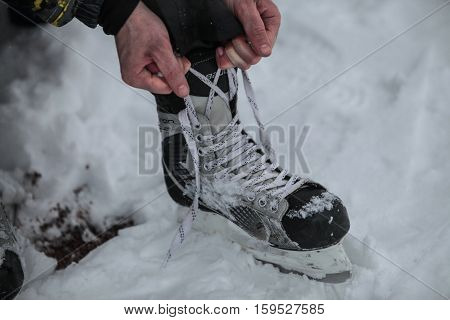 Saint-Petersburg Russia - December 2 2016: Urban outdoor ice rink in the park. Tying skates before going on the ice.