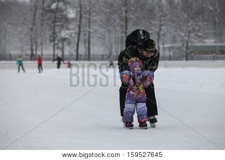 Saint-Petersburg Russia - December 2 2016: Urban outdoor ice rink in the park. Father teaching his child to skate.