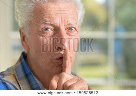 Portrait of senior man presses his finger on mouth asks for silent