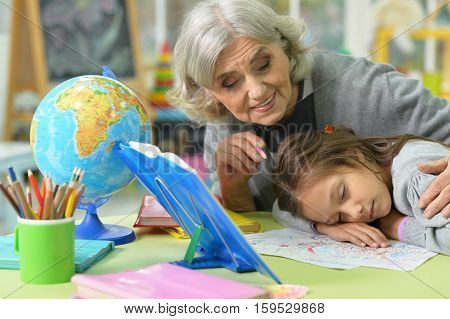 Potrait of grandmother with her granddaughter drawing, little girl fell asleep