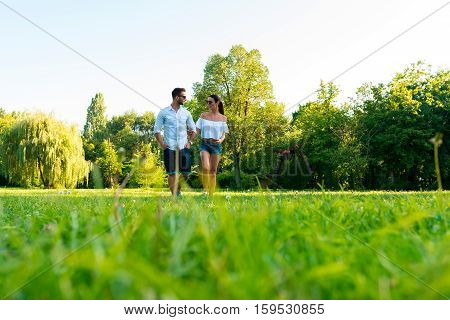 A beautiful young european couple having a walk together in a park in the sunset.