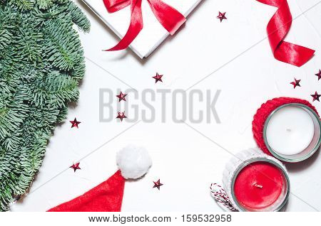 Flat lay Top view Christmas composition isolated on white background. Natural green pine wreath white gift box with red fabric tape spiral ribbon stars confetti candels. Xmas background. Decor table.