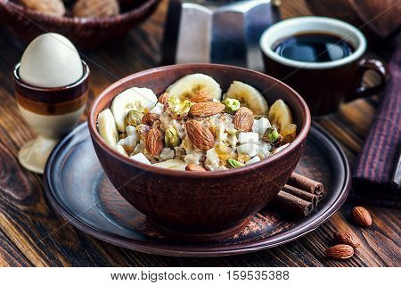 Organic oatmeal porridge with bananas, honey, almonds, pistachio, coconut, kiwi fruit, cinnamon, raisins in dark ceramic bowl with cup of coffee. Healthy breakfast and diet concept on wooden table.