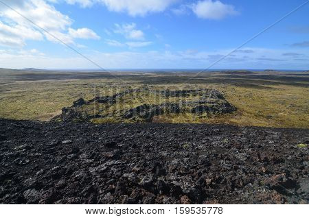 A volcanic crater surrounded by moss covered lava rock from a previous lava flow.