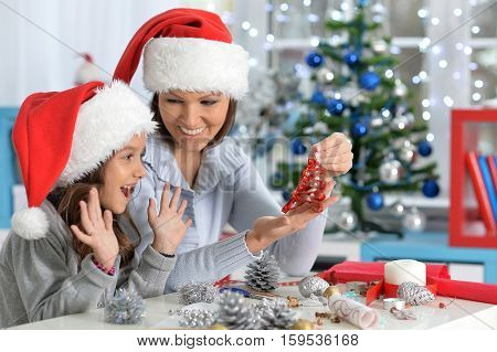 Portrait of happy mother and daughter in Sahta hats preparing for Christmas