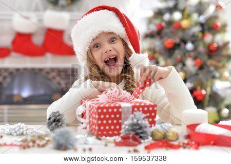 Portrait of happy little girl in Santa hat with het present