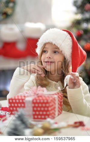 Portrait of smiling little girl in Santa hat with het present