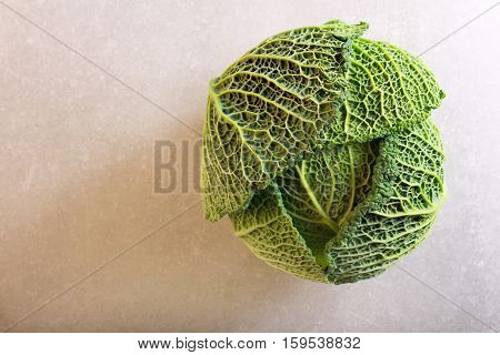 Savoy cabbage over grey background top view