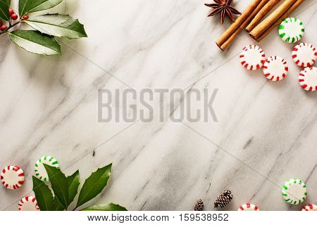 Holiday background with peppermint candy and spices on marble