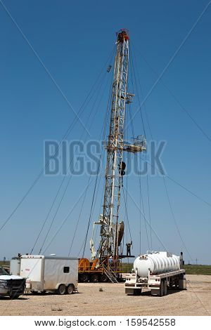 Oil drilling crew called roughnecks work a derrick rig in the oil well fields.