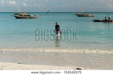 ZANZIBAR, TANZANIYA- JULY 13: man carrying fish on the African seashore with boats on the background near fishing village on July 13, 2016 in Zanzibar