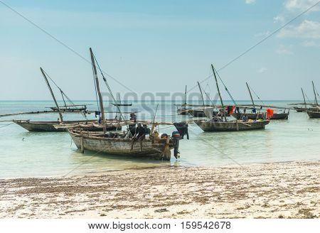 ZANZIBAR, TANZANIYA- JULY 10: fishermen near their sailboat on the shore on July 10, 2016 in Zanzibar